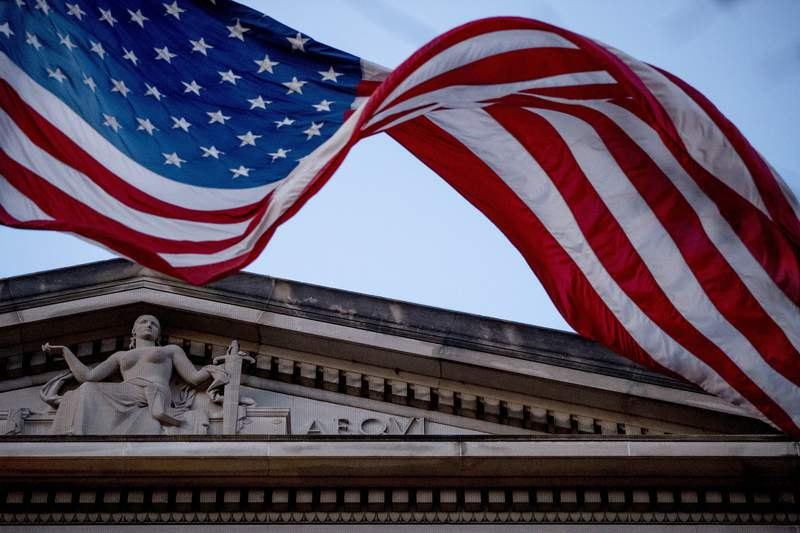 FILE - In this March 22, 2019 file photo, an American flag flies outside the Department of Justice in Washington.The Justice Department has assembled a task force to confront ransomware after what officials say was the most costly year on record for the crippling cyberattacks.  (AP Photo/Andrew Harnik)