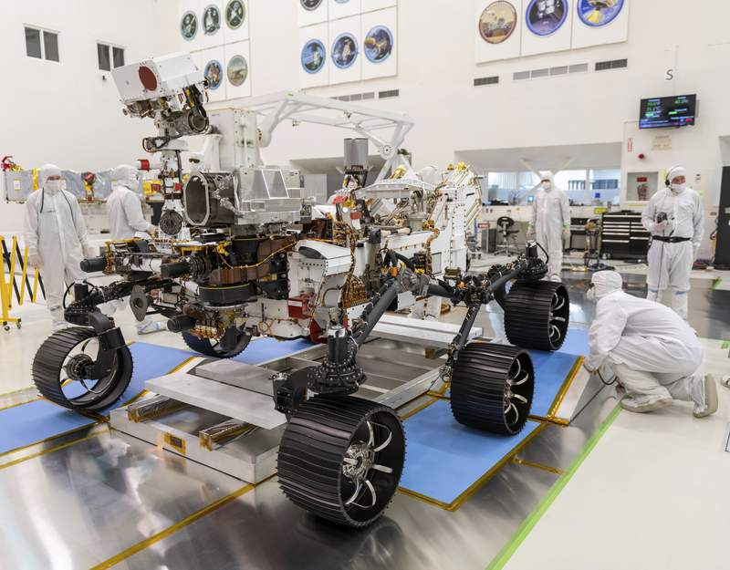 FILE - In this Dec. 17, 2019, file photo made available by NASA, engineers watch the first driving test for the Mars 2020 rover Perseverance. in a clean room at the Jet Propulsion Laboratory in Pasadena, Calif. NASA has delayed the launch of its newest Mars rover yet again because of rocket issues. The space agency has until mid-August to send the Perseverance rover to the red planet to look for signs of ancient microscopic life, before having to wait until 2022. Managers are now targeting no earlier than July 30 for a liftoff from Cape Canaveral, Florida, eating up half of the month-long launch window. (J. Krohn/NASA via AP, File)