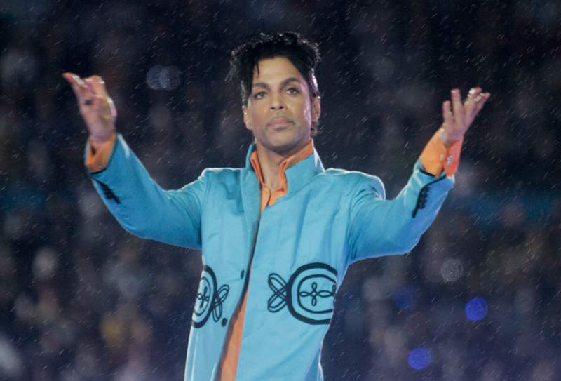 """FILE - This Feb. 4, 2007 file photo shows Prince performing during the halftime show at the Super Bowl XLI football game at Dolphin Stadium in Miami. John Legend, Foo Fighters, Alicia Keys, Chris Martin, H.E.R. and Earth, Wind & Fire are set to perform at a Prince tribute concert this month. The Recording Academy announced Thursday that """"Let's Go Crazy: The GRAMMY Salute to Prince will tape at the Los Angeles Convention Center on Jan. 28, two days after the 62nd annual Grammy Awards. Prince died on April 21, 2016. (AP Photo/David J. Phillip, File)"""