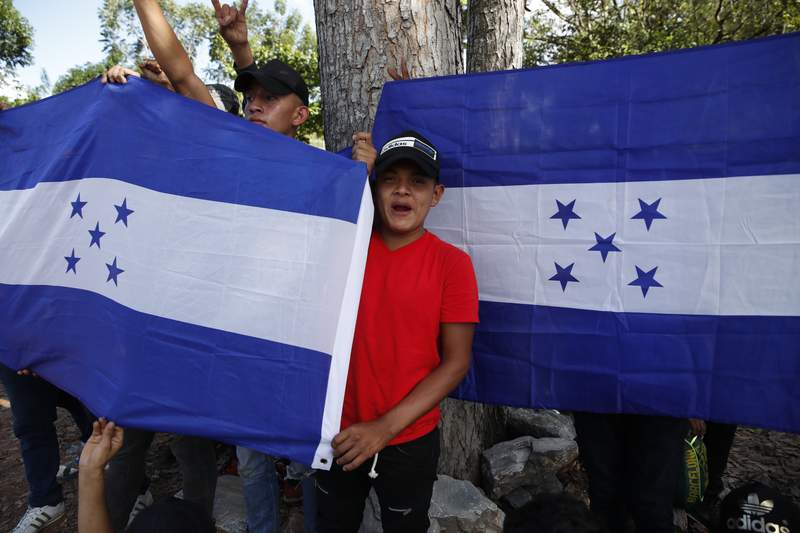 Honduran migrants trying to reach the United States hold up Honduran flags while they are stopped by Guatemalan National Police after crossing the Honduran border, in Morales, Guatemala, Wednesday, Jan. 15, 2020. Migrants in the group said they left Honduras very late Tuesday, around midnight. (AP Photo/Moises Castillo)