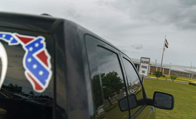 A pickup truck with a Confederate flag-themed decal is parked outside the Reception and Medical Center, the state's prison hospital where new inmates are processed, in Lake Butler, Fla. In 2013, at a prison dorm room in the facility, Warren Williams, a Black inmate who suffered from severe anxiety and depression, found himself in front of Thomas Driver, a white prison guard, after he lost his identification badge, a prison infraction.