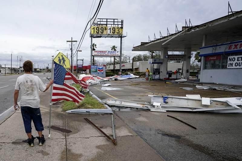 Dustin Amos walks near debris at a gas station on Thursday, Aug. 27, 2020, in Lake Charles, La., after Hurricane Laura moved through the state. (AP Photo/Gerald Herbert)