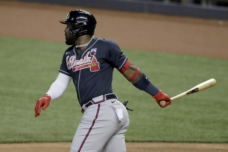 FILE - In this Aug. 16, 2020, file photo, Atlanta Braves' Marcell Ozuna watches his single during the first inning of a baseball game against the Miami Marlins in Miami. The Braves are bringing back Ozuna, signing the slugger to a $65 million, four-year contract. The Braves announced the deal for the 2020 NL home run and RBI leader Friday night, Feb. 5, less than two weeks before pitchers and catchers are set to report for spring training. The deal includes a fifth-year club option for $16 million with a $1 million buyout. (AP Photo/Lynne Sladky, File)