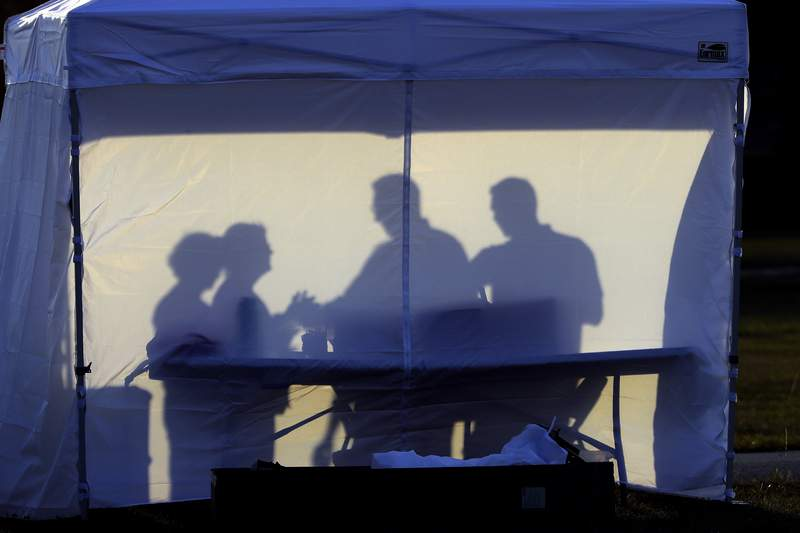 Medical personnel are silhouetted against the back of a tent before the start of coronavirus testing in the parking lot outside of Raymond James Stadium on Wednesday in Tampa. (Photo by Chris O'Meara)