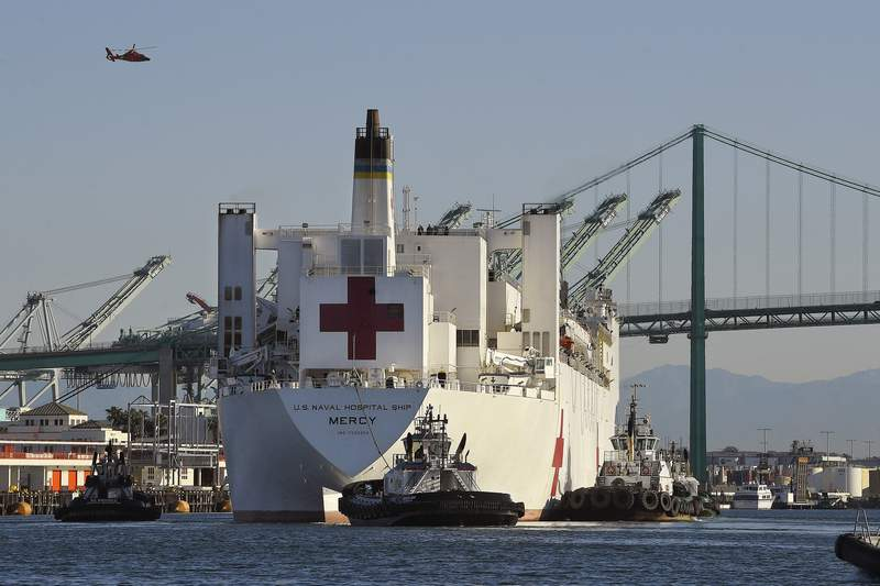 FILE - In this March 27, 2020 file photo, the USNS Mercy hospital ship enters the Port of Los Angeles. The number of COVID-19 cases among crewmembers of the Mercy has risen to seven while it is docked in the Port of Los Angeles to help serve the region's patients who have not been stricken by the coronavirus. A 3rd Fleet spokesman said the seven have been isolated off the ship and the Mercy's ability to receive patients has not been affected. (AP Photo/Mark J. Terrill, File)