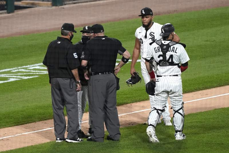 Chicago White Sox manager Rick Renteria, second from left, argues with umpires as catcher Yasmani Grandal, right, and relief pitcher Jimmy Cordero react during the seventh inning of a baseball game against the Chicago Cubs in Chicago, Friday, Sept. 25, 2020. Cordero ejected by home plate umpire Dan Bellino. (AP Photo/Nam Y. Huh)