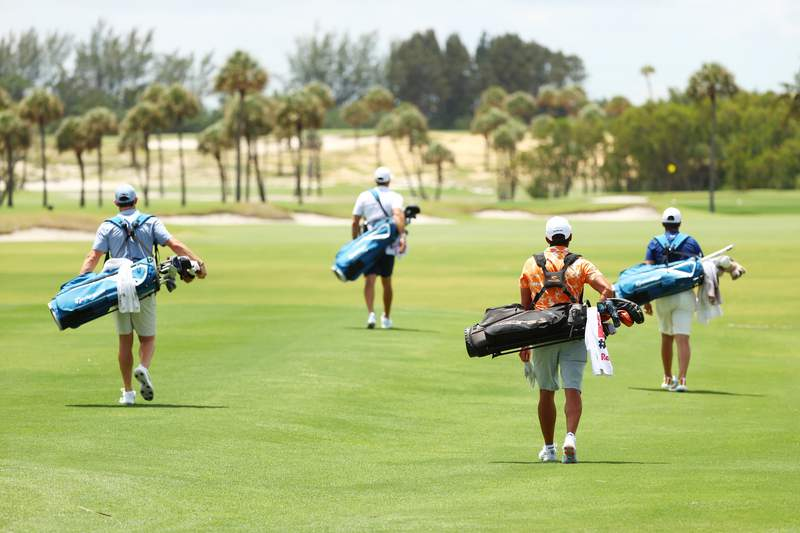 JUNO BEACH, FLORIDA - MAY 17: (L-R) Rory McIlroy of the American Nurses Foundation team, Dustin Johnson of the American Nurses Foundation team, Rickie Fowler of the CDC Foundation team and Matthew Wolff of the CDC Foundation team walk down the first fairway during the TaylorMade Driving Relieve Supported By UnitedHealth Group on May 17, 2020 at Seminole Golf Club in Juno Beach, Florida. (Photo by Mike Ehrmann/Getty Images)