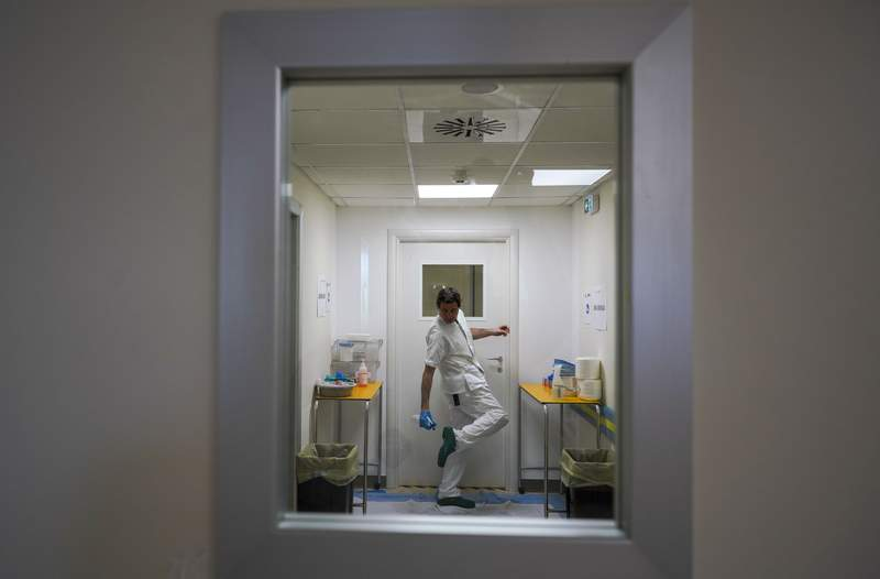 A doctor disinfects his shoes as he leaves the ICU unit of Rome's San Filippo Neri Hospital's Covid department, in Rome, Thursday, April 9, 2020. (AP Photo/Andrew Medichini)