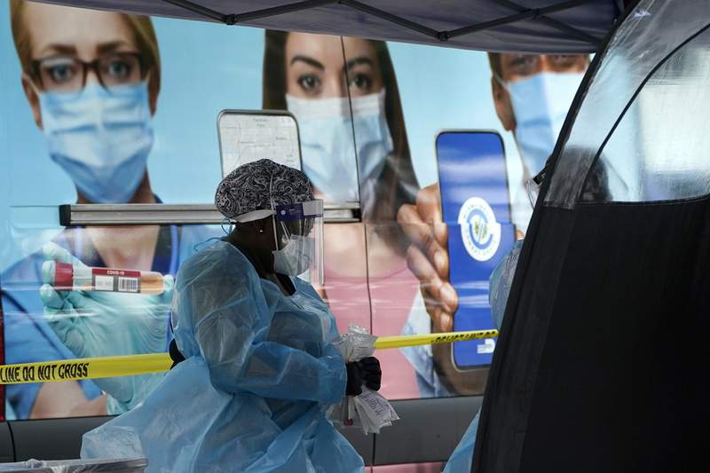 A health care employee works at a walk-up COVID-19 testing site, Wednesday, Nov. 18, 2020, in Miami. Florida health officials have reported a steady increase in the number of new coronavirus cases each day over the past month and a half, though the numbers are no where near the peak in July.(AP Photo/Lynne Sladky)