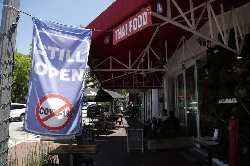 """A sign reading """"Still Open"""" hangs outside of Atchana's Homegrown Thai restaurant in Miami."""