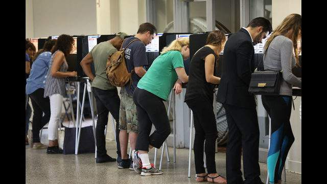 Voters fill out their ballots as they cast their vote at a polling station in November 2018.