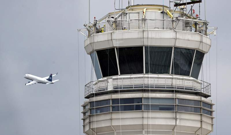 FILE - In this March 24, 2011, file photo, a passenger jet flies past the FAA control tower at Ronald Reagan Washington National Airport in Arlington, Va. The U.S. government will pay nearly $44 million to settle an age-discrimination case filed 16 years ago on behalf of hundreds of workers who missed out on federal pensions after their jobs were outsourced. (AP Photo/Cliff Owen, File)
