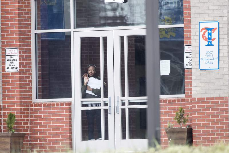 A student waits at the front entrance at Woodland Middle School in East Point, Ga., on Monday, The Fulton County School system decided to close schools on Tuesday after a teacher who taught at that school and two others tested positive with the coronavirus. (AP photo)