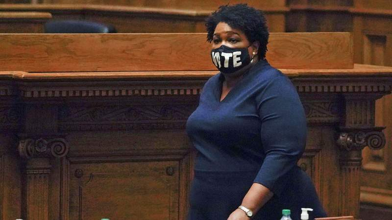 Democrat Stacey Abrams walks on Senate floor before of members of Georgia's Electoral College cast their votes at the state Capitol on Monday.