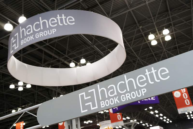 FILE - This May 28, 2015 file photo shows signs for Hachette Book Group displayed at BookExpo America in New York. Publishing's annual national convention, BookExpo, has been canceled. The announcement Tuesday by ReedPop comes after the gathering already had been postponed from May to July because of the coronavirus outbreak (AP Photo/Mark Lennihan, File)