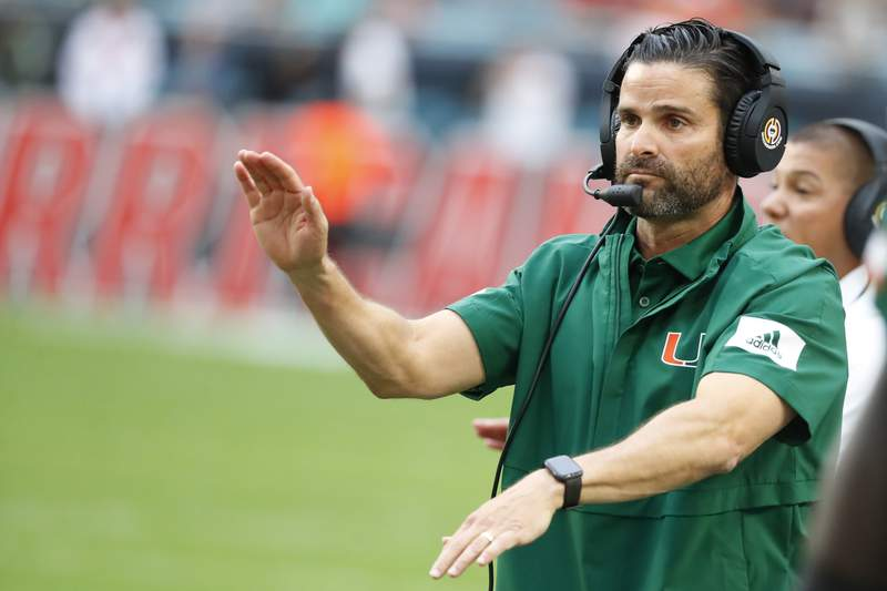 In this Saturday, Nov. 9, 2019 file photo, Miami head coach Manny Diaz calls out a play during the first half of an NCAA college football game against Louisville in Miami Gardens, Fla. Miami coach Manny Diaz told The Associated Press on Monday, Feb. 3, 2020 that he believes the Hurricanes are already better than they were when last season's 6-7 debacle ended. Diaz says the Hurricanes have improved their roster and their coaching staff, both by additions and subtractions. He also drew a parallel to the culture that the Miami Heat have stuck with in their bounceback season this year.  (AP Photo/Wilfredo Lee, File)