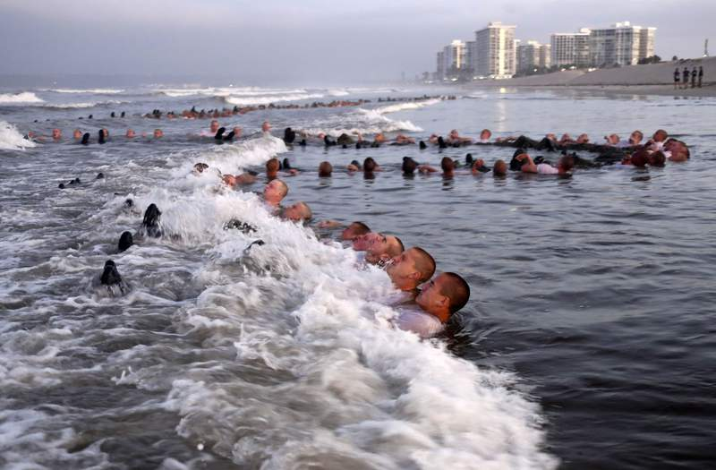 """FILE - In this May 4, 2020 photo provided by the U.S. Navy, SEAL candidates participating in """"surf immersion"""" during Basic Underwater Demolition/SEAL (BUD/S) training at the Naval Special Warfare (NSW) Center in Coronado, Calif. For the first time, a female sailor has successfully completed the grueling 37week training course to become a Naval Special Warfare combatant-craft crewman  the boat operators that transport Navy SEALs and conduct their own missions at sea. Navy officials said they would not identify the woman, who completed the final phases of training and graduated Thursday. She was one of 17 sailors to receive their pins during the ceremony.  (MC1 Anthony Walker/U.S. Navy via AP)"""