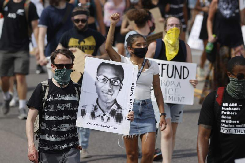FILE - In this June 27, 2020 file photo, demonstrators carry placards as they walk down Sable Boulevard during a rally and march over the death of Elijah McClain in Aurora, Colo. On Friday, Jan. 8, 2021, the Colorado attorney general opened a grand jury investigation into the death of McClain, a 23-year-old Black man who was stopped as he walked down the street, placed in a neck hold, and injected with a sedative in 2019. (AP Photo/David Zalubowski, File)