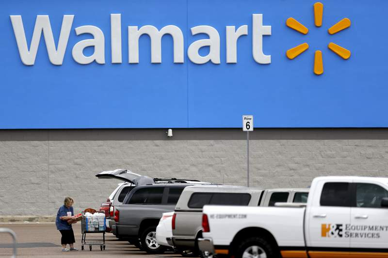 FILE - In this March 31, 2020 file photo, a woman pulls groceries from a cart to her vehicle outside of a Walmart store in Pearl, Miss. Walmart has reversed course, announcing Friday, Oct. 30 it is returning ammunition and firearms to their displays in its U.S. stores. The nations largest retailer had previously said it had removed the items from displays due to civil unrest in some areas of the country but said Friday the items had been restored to displays because the unrest has remained isolated. (AP Photo/Julio Cortez, File)