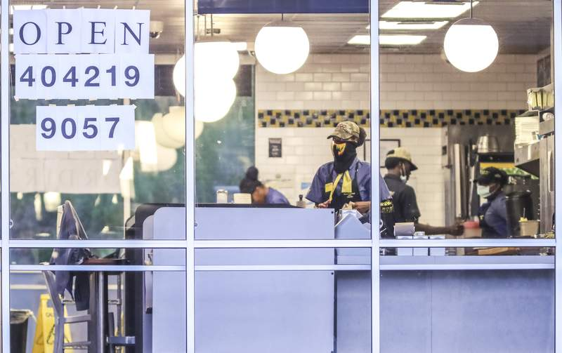 Waffle House employees opened the dining room on Monday, April 27, 2020 at the Waffle House at 860 Glenwood Ave SE in Atlanta. Restaurants around metro Atlanta began to reopen dining rooms Monday, April 27, 2020 as restrictions related to the coronavirus pandemic are lifted. Restaurants will be allowed to operate with in-person dining as long as they follow a set of 39 guidelines laid out by the state government, which include a requirement that all employees wear masks, a maximum of 10 customers per 500 square feet of floor space and a maximum of six diners per table. (John Spink/Atlanta Journal-Constitution via AP)