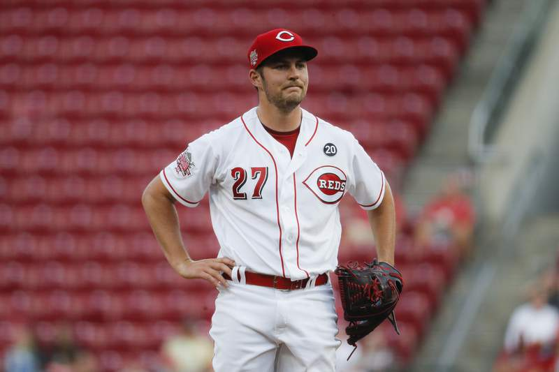 FILE - In this Aug. 19, 2019 file photo Cincinnati Reds starting pitcher Trevor Bauer reacts after walking San Diego Padres' Josh Naylor in the first inning of a baseball game in Cincinnati. Bauer sent a series of tweets during the weekend, starting with a jab about Major League Baseball's threat to cut ties with minor league affiliates. Bauer followed up with: At least Rob Manfred is trying to ruin baseball at all levels and isn't discriminating. MLB had no immediate comment to Bauer's remarks, Sunday, Dec. 15, 2019. Manfred recently said MLB was pushing ahead with a rules change for 2020 that requires pitchers to face at least three batters or finish a half-inning. (AP Photo/John Minchillo)