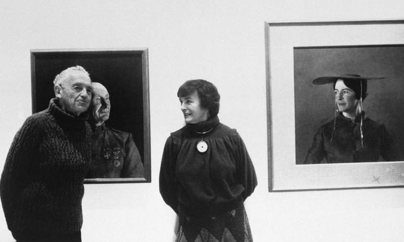 """FILE - In this May 1985 file photo, American artist Andrew Wyeth poses with his wife Betsy at an unknown location in front of his paintings """"The Patriot,"""" left, and """"Maga's Daughter"""" for which Betsy was the model. Betsy James Wyeth, the widow, business manager and muse of painter Andrew Wyeth, died Tuesday, April 21, 2020, at age 98, according to the Brandywine River Museum of Art in Chadds Ford, Pa., which she helped found. (AP Photo, File)"""