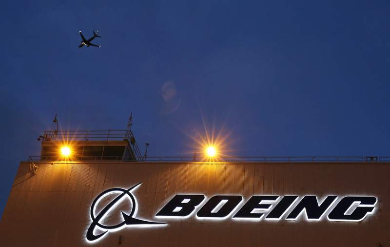FILE- In this Oct. 19, 2015, file photo, an airplane flies over a sign at Boeing's newly expanded 737 delivery center at Boeing Field in Seattle. Federal regulators have imposed $5.4 million in civil penalties against Boeing on Thursday, Feb. 25, 2021, for violating terms of a $12 million settlement in 2015, and the aircraft maker has agreed to pay another $1.21 million to settle two current enforcement cases. (AP Photo/Ted S. Warren, File)