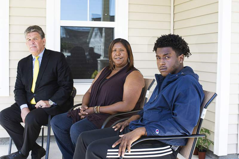 In this Thursday, May 7, 2020, photo, provided by the Port City Daily, high school senior Dameon Shepard, right, his mother, Monica Shepard, and their attorney Jim Lea, left, pose for a photo at the Shepard's home in the Rocky Point area of Pender County, in North Carolina. New Hanover County Sheriff's Deputy Jordan Kita faces criminal charges after authorities say he led a group of people to the wrong location, the Shepards' home, in a search for a missing girl. Kita has also been fired. (Mark Darrough/Port City Daily via AP)