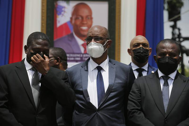 FILE - In this July 20, 2021 file photo, Haiti's designated Prime Minister Ariel Henry, center, and interim Prime Minister Claude Joseph, right, pose for a group photo with other authorities in front of a portrait of slain Haitian President Jovenel Moise at the National Pantheon Museum during a memorial service for Moise in Port-au-Prince, Haiti. Haitis chief prosecutor has asked a judge to charge Henry in the slaying of his predecessor and barred him from leaving the country. (AP Photo/Joseph Odelyn, File)
