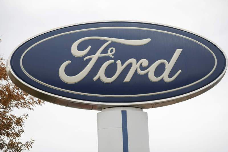 FILE - In this Oct. 20, 2019, file photo, the company logo stands over a long row of unsold vehicles at a Ford dealership in Littleton, Colo. Ford Motor Co.'s profit in 2019 plunged by more than $3.6 billion, weighed down by slowing U.S. sales, the cost of a botched SUV launch and some big pension expenses. (AP Photo/David Zalubowski, File) (Copyright 2019 The Associated Press. All rights reserved.)