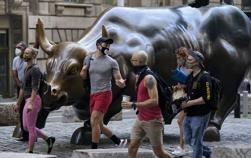 FILE - In this Tuesday, Sept. 8, 2020, file photo, people wearing masks pass the Charging Bull statue in New York's financial district. Wall Street is steadying itself Wednesday following its first three-day losing streak in nearly three months, as the bloodletting for big technology stocks comes to at least a temporary halt. (AP Photo/Mark Lennihan, File)