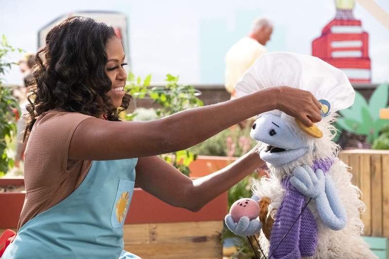 """This image released by Netflix shows former first lady Michelle Obama putting a chef's hat on Waffles, a furry puppet with waffle ears and holding Mochi, a pink round puppet, on the set of the children's series """"Waffles + Mochi."""" Obama is launching the new Netflix childrens food show on March 16. (Adam Rose/Netflix via AP)"""
