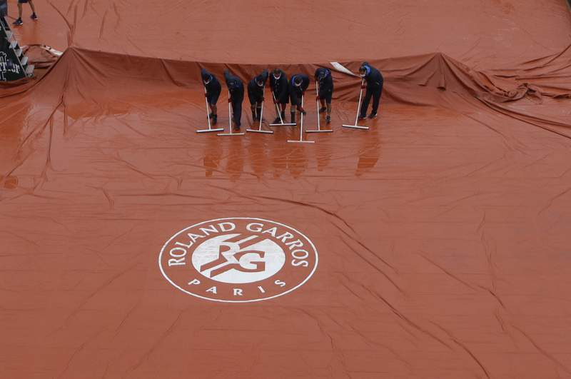Stadium workers remove rain water from the cover of Suzanne Lenglen court as rain delayed fourth round matches of the French Open tennis tournament at the Roland Garros stadium in Paris, France, Monday, Oct. 5, 2020. (AP Photo/Alessandra Tarantino)