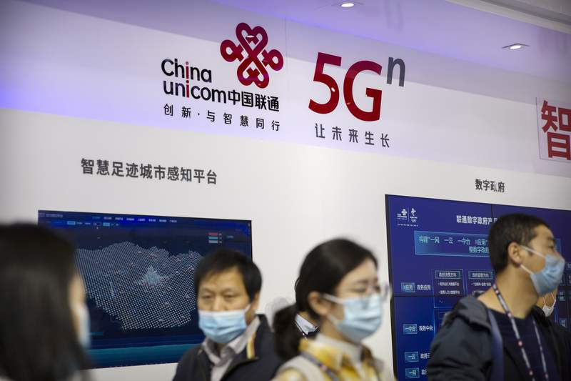FILE - In this Oct. 14, 2020, file photo, people wearing face masks to protect against the coronavirus look at a display from Chinese telecommunications firm China Unicom at the PT Expo in Beijing. China's government on Thursday called on Washington to drop efforts to expel three state-owned Chinese phone companies, including China Unicom Americas, a unit of China Unicom, from the United States in a new clash over technology and security. (AP Photo/Mark Schiefelbein, File)