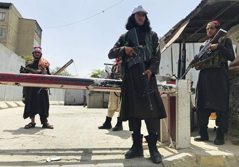 Taliban fighters stand guard at a checkpoint near the US embassy that was previously manned by American troops, in Kabul, Afghanistan, on Tuesday.