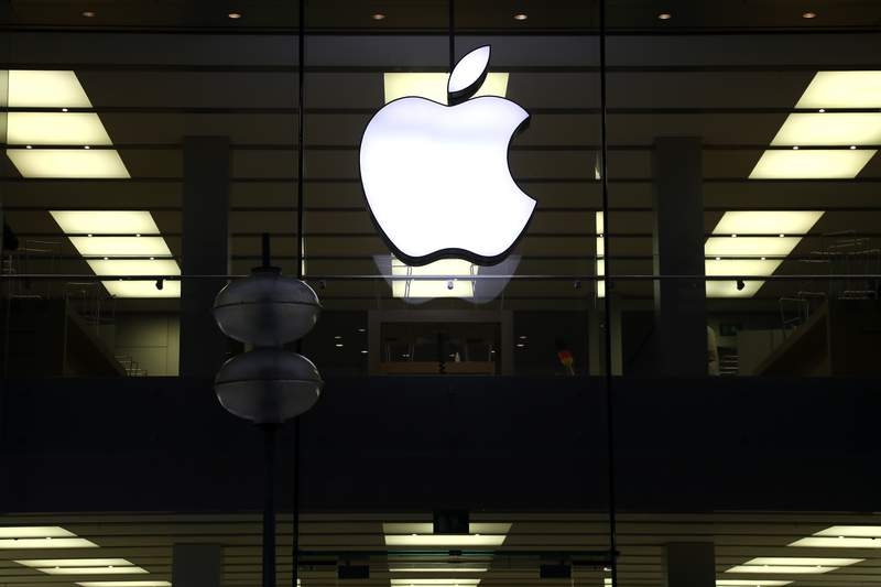 FILE - This Dec. 16, 2020 file photo shows an illuminated Apple logo at a store in Munich, Germany. Apple is following through on its pledge to crack down Facebook and other snoopy apps that secretly shadow people on their iPhones to help sell more advertising. The new privacy feature, dubbed App Tracking Transparency, rolled out Monday, April 26, 2021, as part of an update to the operating system powering the iPhone and iPad.  (AP Photo/Matthias Schrader, File)