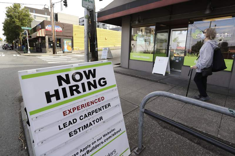 FILE - In this June 4, 2020 file photo, a pedestrian wearing a mask walks past a reader board advertising a job opening for a remodeling company, in Seattle. U.S. companies added nearly 2.4 million jobs in June, according to a private survey, a large gain that still leaves the job market far below its pre-pandemic levels. The payroll company ADP said that small businesses reported the largest gain, adding 937,000 jobs. Construction firms and restaurants and hotels also posted big increases in hiring. (AP Photo/Elaine Thompson, File)