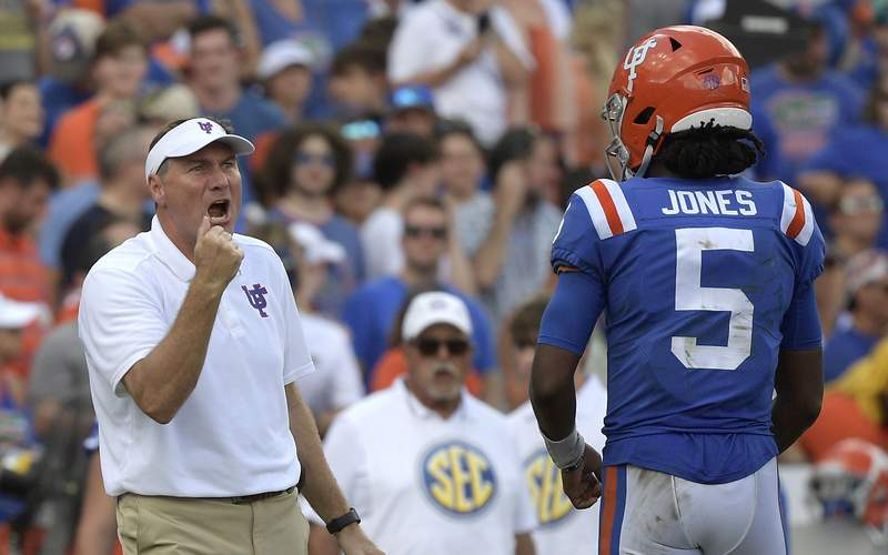 Florida head coach Dan Mullenv calls out instructions in front of quarterback Emory Jones during the second half of an NCAA college football game against Vanderbilt, Saturday, Oct. 9, 2021, in Gainesville.