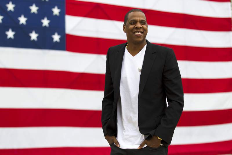 """FILE - In this May 14, 2012 file photo, entertainer Shawn """"Jay-Z"""" Carter smiles in between interviews, after a news conference at Philadelphia Museum of Art in Philadelphia. Jay-Zs annual festival in Philadelphia, Made in America, wont take place Labor Day weekend due to the coronavirus pandemic. In a statement Wednesday, July 1, 2020, the rap moguls Roc Nation company said they plan to produce the popular festival in 2021. (AP Photo/Matt Rourke, file)"""