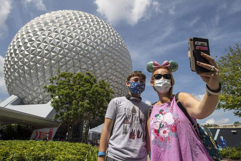 Guests stop for a selfie in front of Spaceship Earth, July 15, 2020, at EPCOT at Walt Disney World Resort in Lake Buena Vista, Fla., on the first day of the park's phased reopening. (Kent Phillips, photographer)
