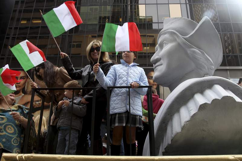 In this Oct. 8, 2012 file photo, people ride on a float with a large bust of Christopher Columbus during the Columbus Day parade in New York.  Monday, Oct. 11, 2021 federal holiday dedicated to Christopher Columbus continues to divide those who view the explorer as a representative of Italian Americans history and those horrified by an annual tribute that ignores the native people whose lives and culture were forever changed by colonialism.