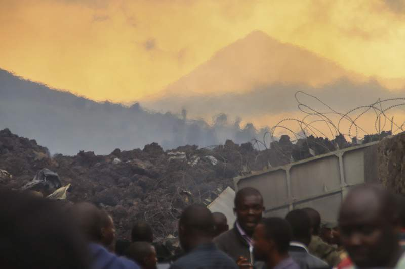 FILE - In this Sunday, May 23, 2021 file photo, residents check the damages caused by lava from the overnight eruption of Mount Nyiragongo, seen in background, in Buhene, on the outskirts of Goma, Congo.  Thousands of people are returning to Goma and a surrounding region in eastern Congo hoping to find their homes intact weeks after a volcano erupted, but fearing the worst. The eruption on May 22 of Mount Nyiragongo forced tens of thousands of people to flee with no warning as lava flowed through their communities. Residents living on the outskirts of the North Kivu provincial capital were forced to evacuate again a week later when fears rose there would be another eruption. (AP Photo/Justin Kabumba, File)
