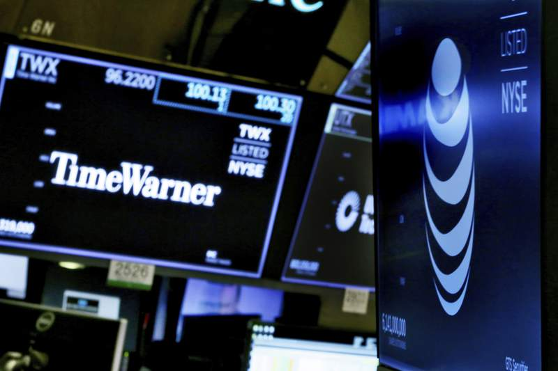 FILE - In this June 13, 2018, file photo, the logos for Time Warner and AT&T appear above alternate trading posts on the floor of the New York Stock Exchange. On Monday, May 17, 2021, AT&T said it will combine its massive WarnerMedia media assets, which includes HBO and CNN, with Discovery Inc. to create a new media heavyweight in a $43 billion deal. (AP Photo/Richard Drew, File)