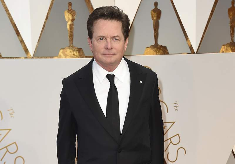 FILE - Michael J. Fox arrives at the Oscars on Feb. 26, 2017, in Los Angeles. Fox will receive an honorary AARP award for his work with a charity that advocates for Parkinson's research. The organization announced Tuesday, Oct. 5, 2021, that Fox will receive the honorary AARP Purpose Prize award during a virtual ceremony on Dec 15. (Photo by Jordan Strauss/Invision/AP, File)