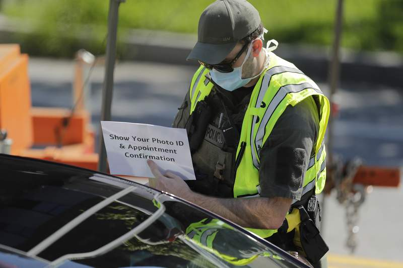 """An official holds a sign telling people to """"Show Your Photo ID and Appointment Confirmation"""" to help guide patients to a COVID-19 testing area on Georgia Tech's campus, Monday, April 6, 2020, in Atlanta. (AP Photo/Brynn Anderson)"""