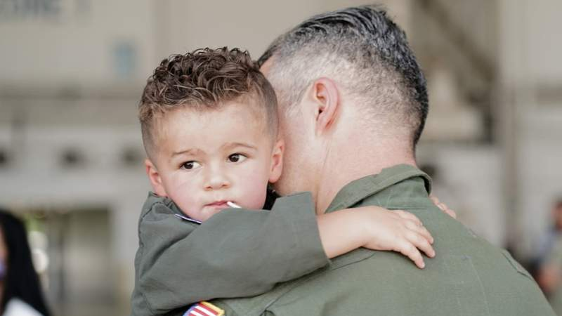 """A boy hugs his father for the first time in six months as the """"Mad Foxes"""" returned to NAS Jacksonville on Tuesday morning."""