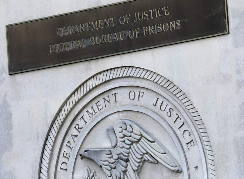 FILE - In this July 6, 2020, file photo a sign for the Department of Justice Federal Bureau of Prisons is displayed at the Metropolitan Detention Center in the Brooklyn borough of New York. While most criminal justice overhauls require action from local officials or legislation, reforming the federal prison system is something President Joe Biden and his Justice Department control. (AP Photo/Mark Lennihan, File)