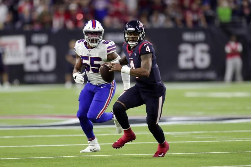 Houston Texans quarterback Deshaun Watson (4) scrambles away from Buffalo Bills defensive end Jerry Hughes (55) during the second half of an NFL wild-card playoff football game Saturday, Jan. 4, 2020, in Houston. (AP Photo/Michael Wyke)