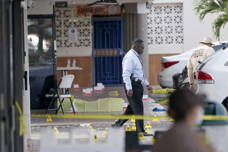 Law enforcement officials work the scene of a shooting outside a banquet hall near Hialeah, Fla., Sunday, May 30, 2021. Two people died and an estimated 20 to 25 people were injured in a shooting outside a banquet hall in South Florida, police said. The gunfire erupted early Sunday at the El Mula Banquet Hall in northwest Miami-Dade County, near Hialeah, police told news outlets. (AP Photo/Lynne Sladky)