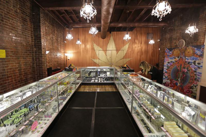 FILE - In this photo taken Dec. 7, 2015, a worker cleans a display case at the Ganja Goddess Cannabis Store in Seattle. On Monday, June 7, 2021, Washington state officials announced that the state's nearly 500 licensed marijuana retailers could begin hosting COVID-19 vaccine clinics and offering a single, free pre-rolled marijuana cigarette to any adult over 21 who receives a shot on-site, but due to federal law and other complications, it's not clear if any of the state's legal pot shops will participate. A current manager at Ganja Goddess said that they would not be participating because they do not have space to host a clinic. (AP Photo/Ted S. Warren, File)